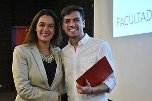 EU Ingrid Allers entregando un reconocimiento al egresado Diego Inostroza, quien hizo su Internado Comunitario en España.