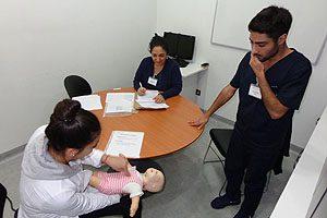 EU Marcia Maldonado evaluando a una estudiante de la asignatura (delantal blanco), en un procedimiento de simulación.