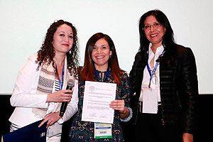 EU Paulina Araya recibiendo un diploma luego de obtener el 3° lugar en los trabajos de investigación oral junto a la EU Mara Muñoz.