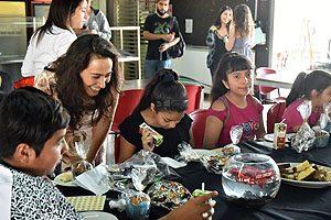 Dra. Milena Soto, Coordinadora de Campos Clínicos de la Escuela de Odontología UDP, junto a algunos de los 12 menores que asistieron al desayuno navideño.